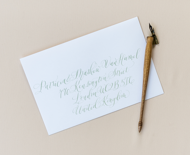 White envelopes with pale green calligraphy